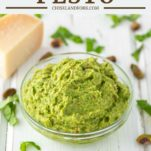 avocado pesto in glass bowl with parmesan cheese in background