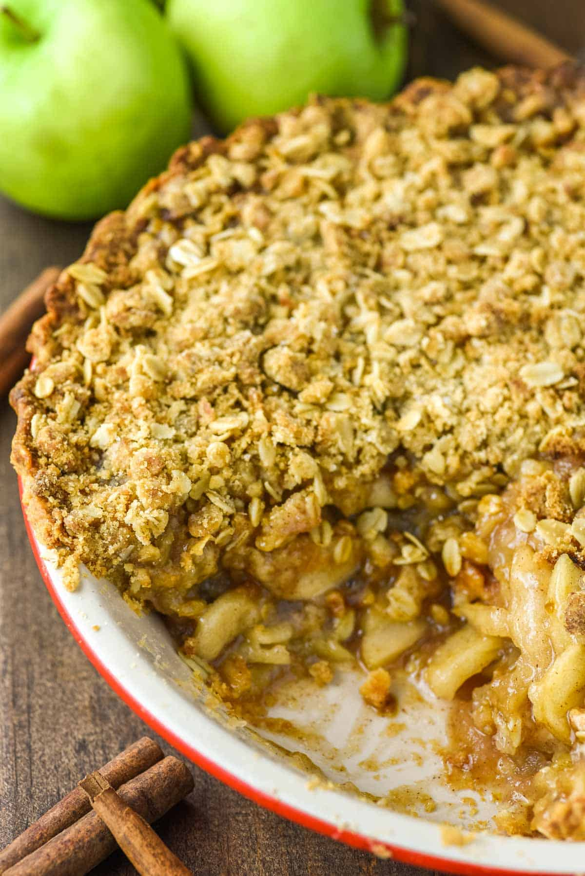 apple pie with crumb topping in red pie dish