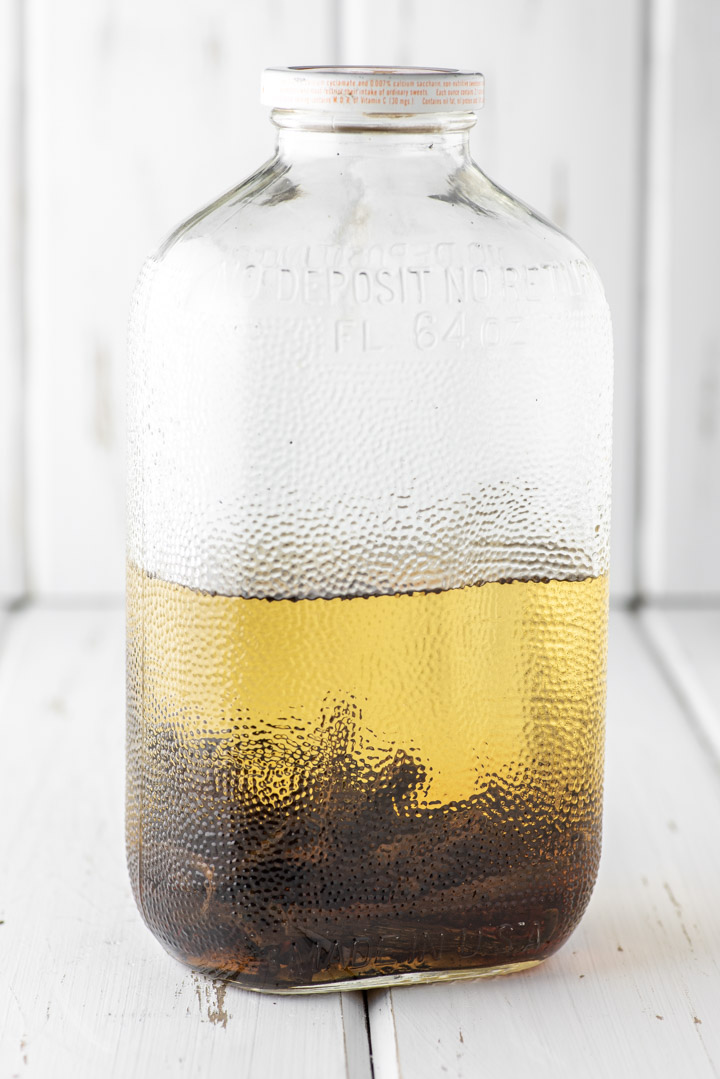 vodka, bourbon and vanilla beans added to glass jar sitting on white table