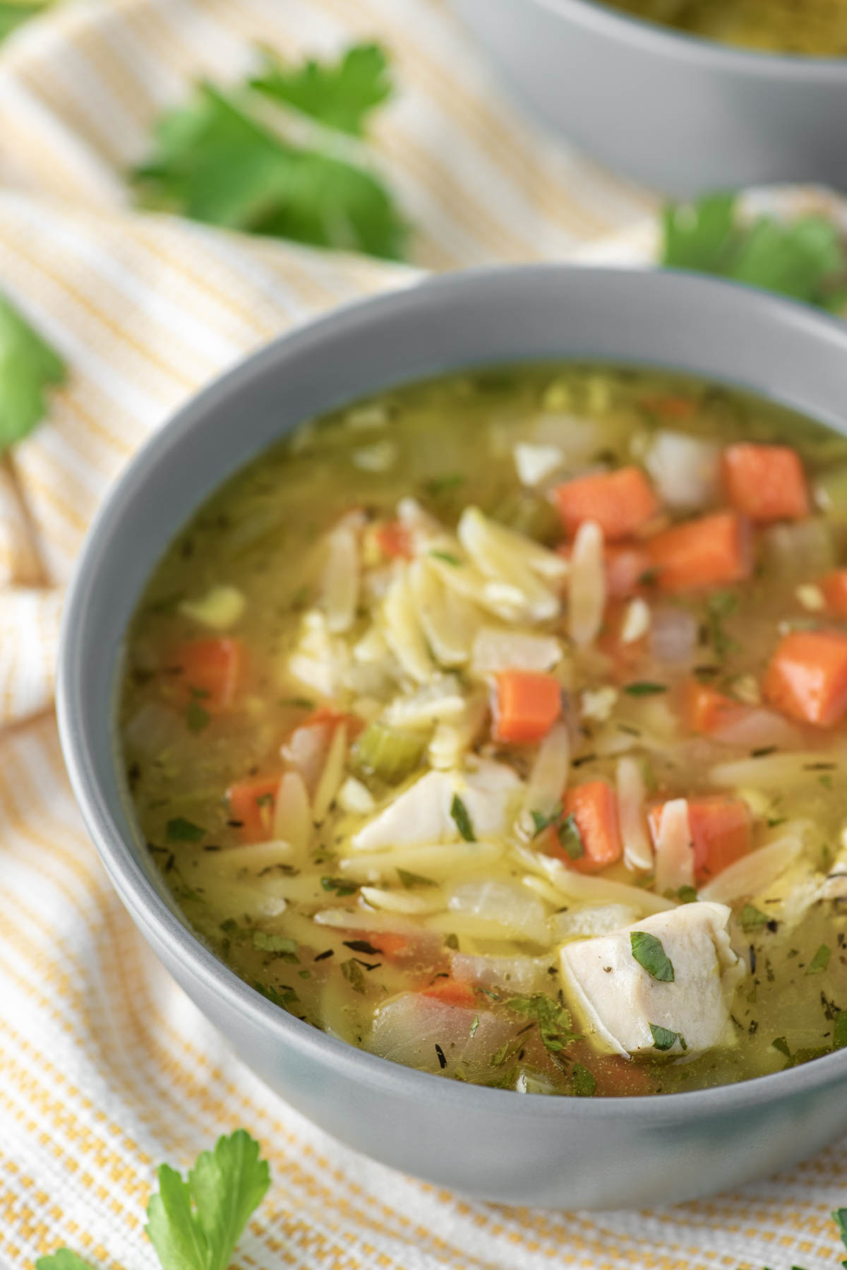 lemon chicken orzo soup in grey bowl