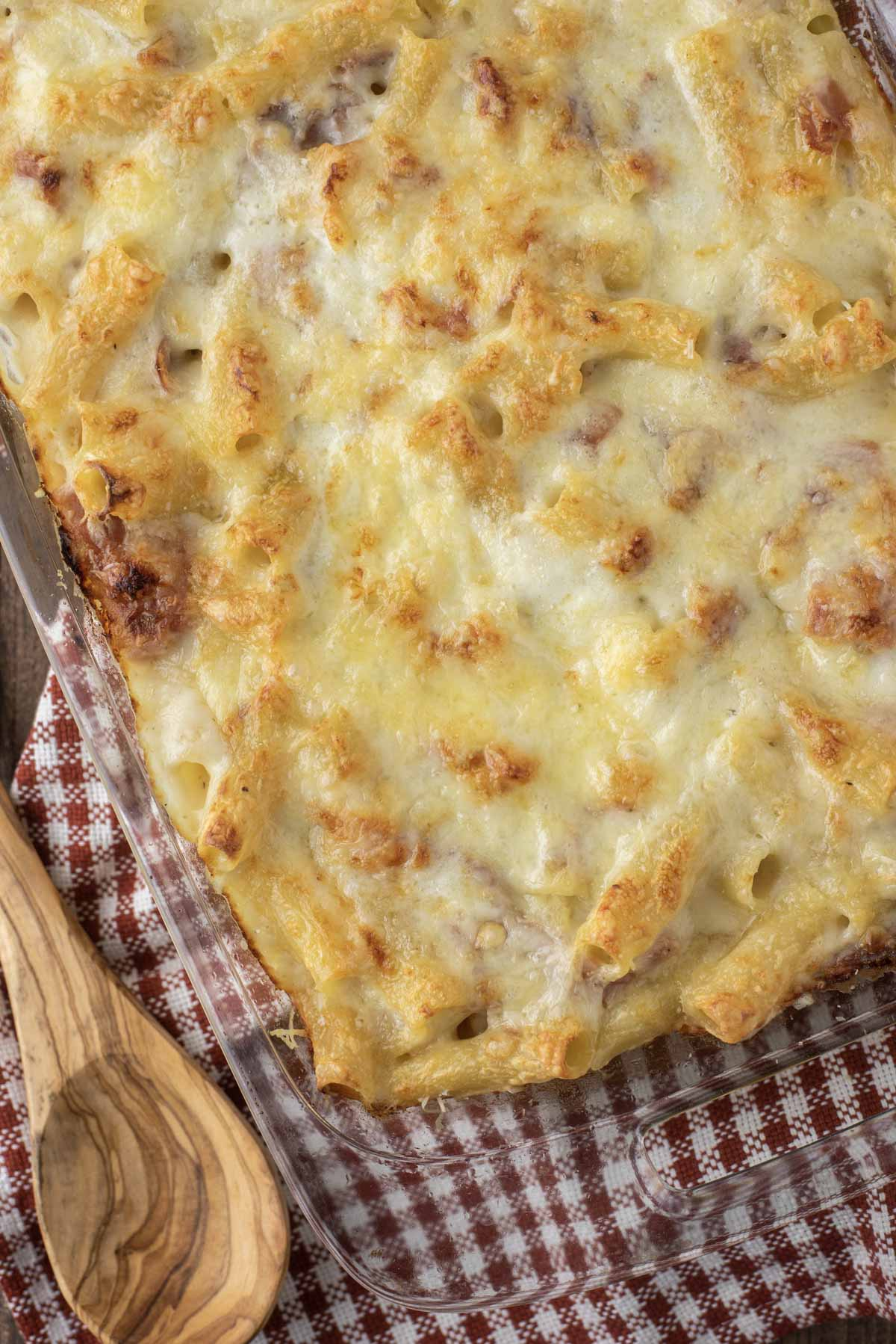 overhead shot of baked rigatoni in glass baking dish with wooden spoon