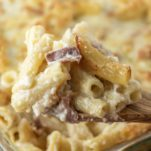 wooden spoon lifting out baked rigatoni from glass baking dish