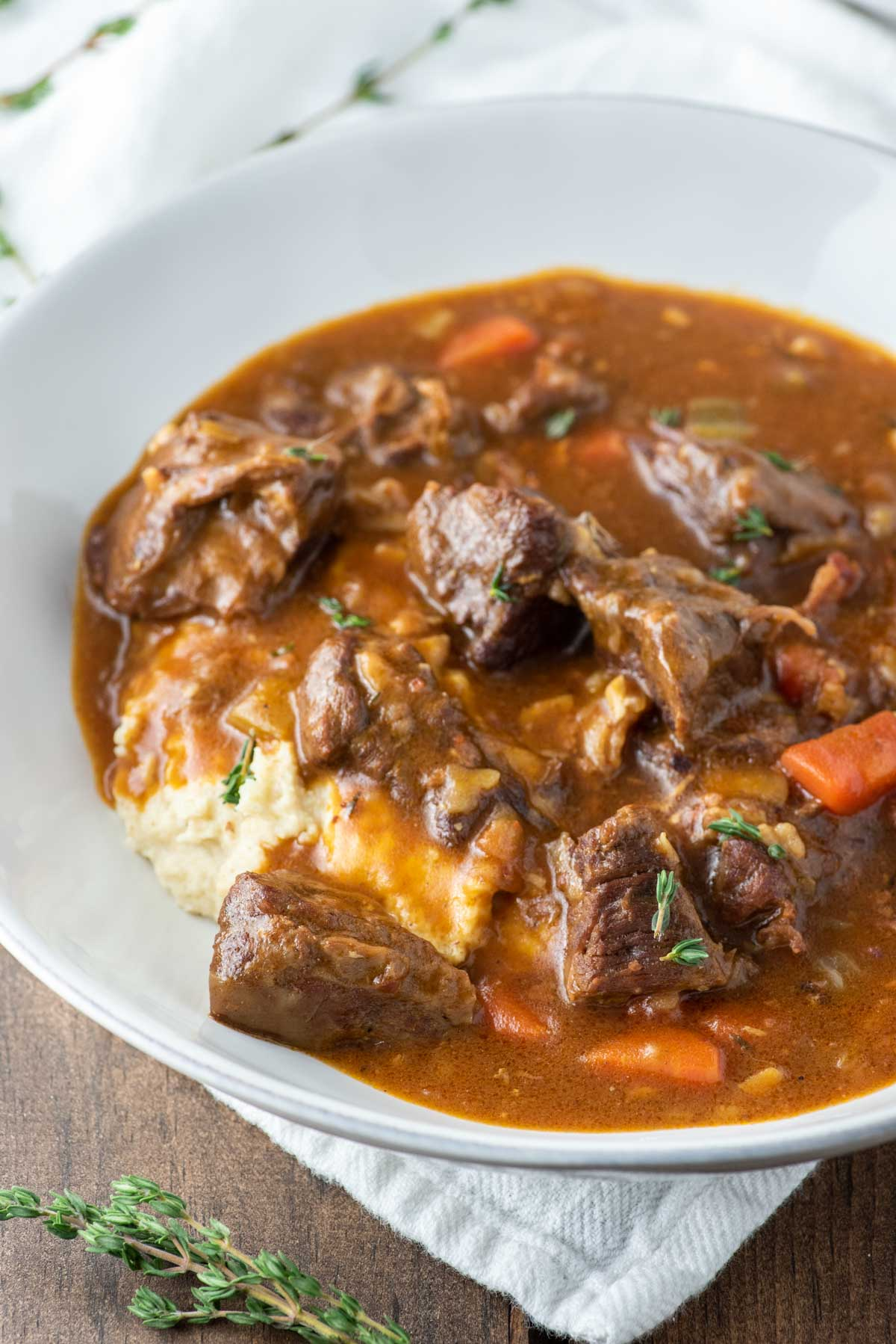 close-up of Guinness beef stew in white bowl with mashed cauliflower