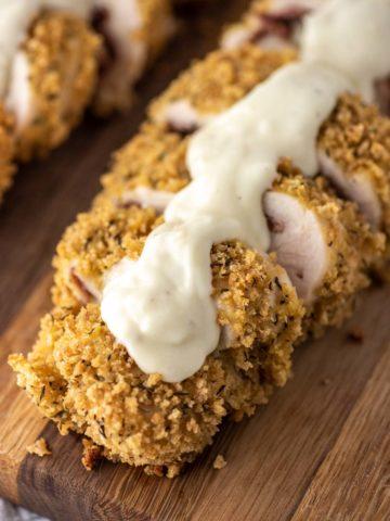 close-up of baked chicken cordon bleu with parmesan cream sauce