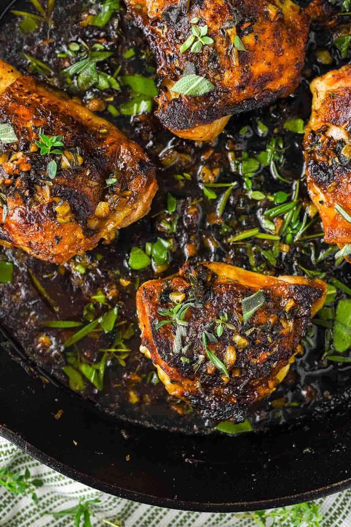 overhead shot of 4 chicken thighs with garlic herb sauce in skillet