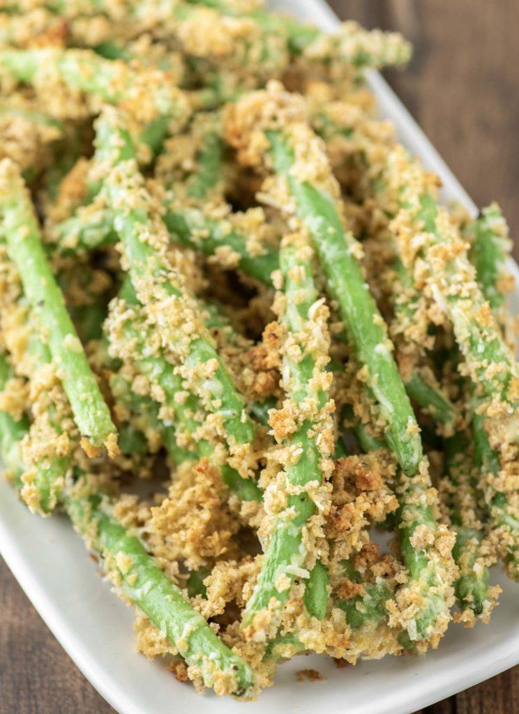 crispy green beans stacked on white plate