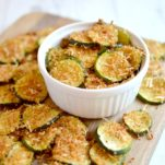 Baked parmesan zucchini chips in small bowl on wood cutting board