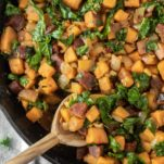 overhead shot of spoon dipped in chorizo sweet potato hash