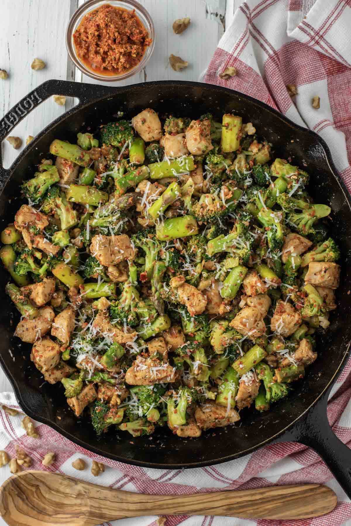 overhead shot of roasted red pepper pesto chicken and veggies in cast iron skillet