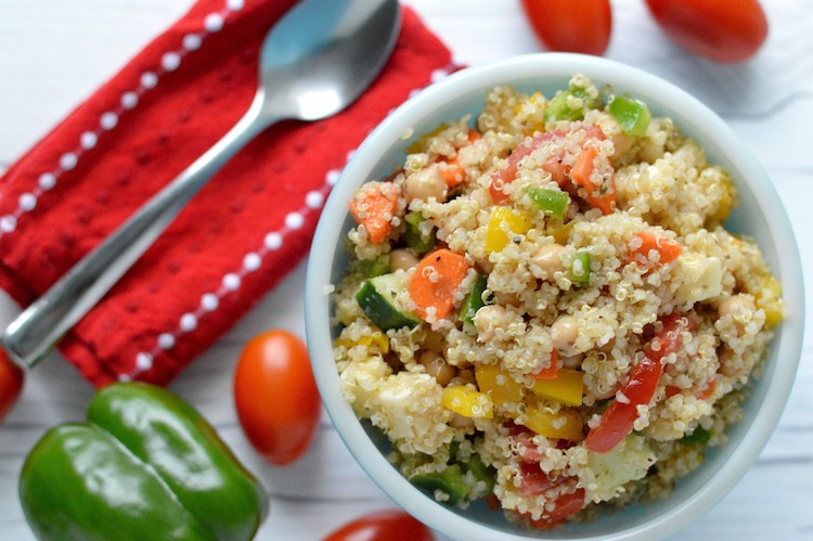 Overhead of summer quinoa salad in blue bowl with tomatoes and green pepper