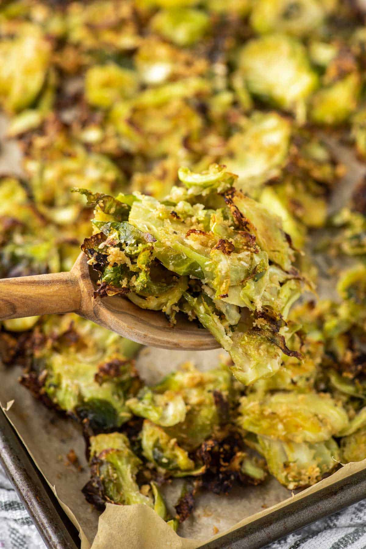 wooden spoon lifting out parmesan roasted Brussel sprouts