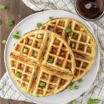 overhead shot of bacon cheddar waffles on white plate with bowl of maple syrup