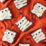 overhead shot of mummy brownies on orange dish towel