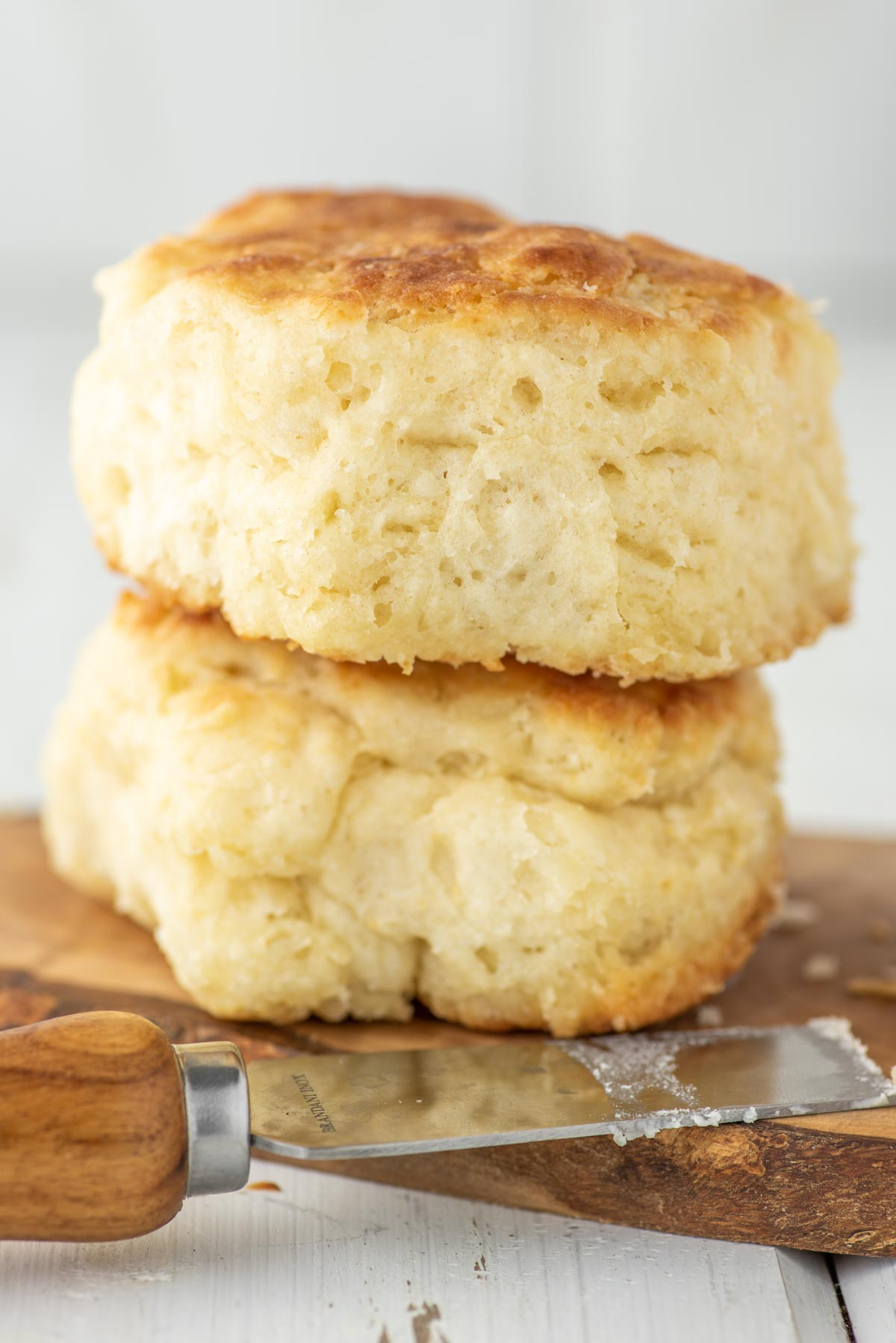 two buttermilk biscuits on wood board with butter knife