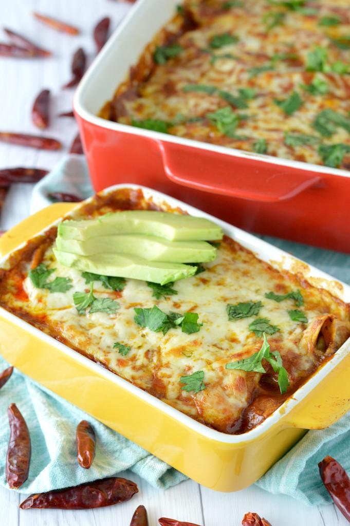 veggie enchiladas in yellow baking dish with red baking dish in background