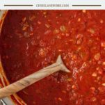 overhead shot of homemade marinara sauce in Dutch oven with wooden spoon dipped in it