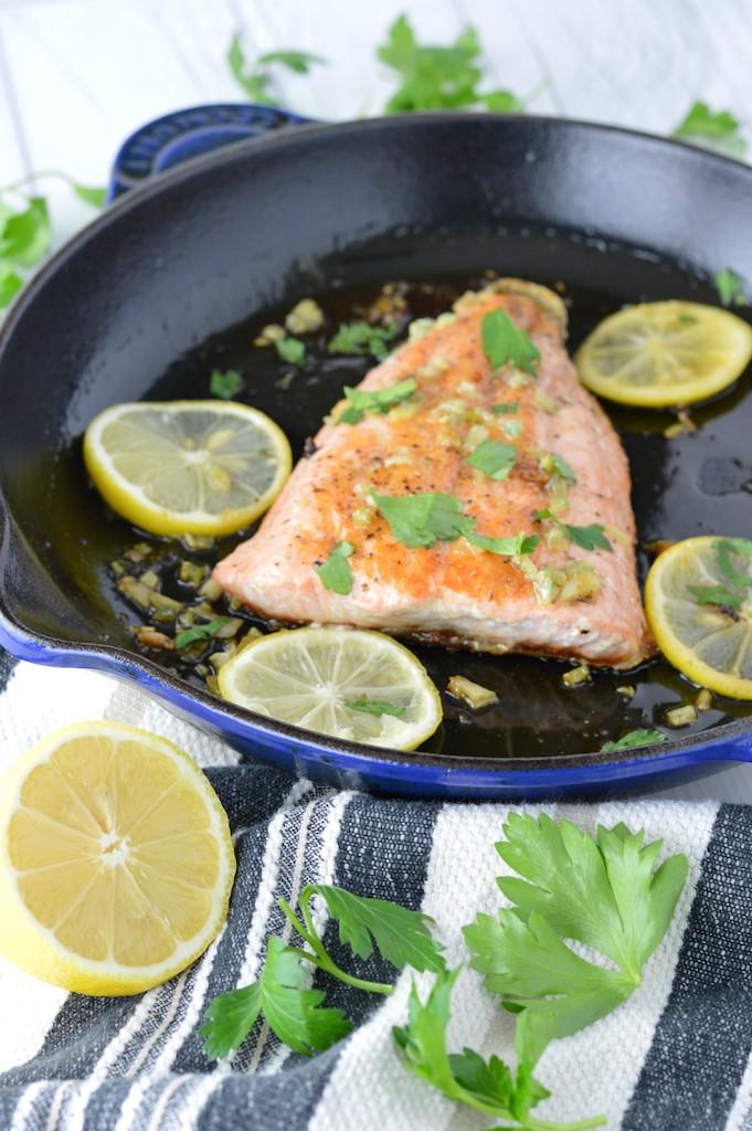 honey salmon in blue skillet with sliced lemons