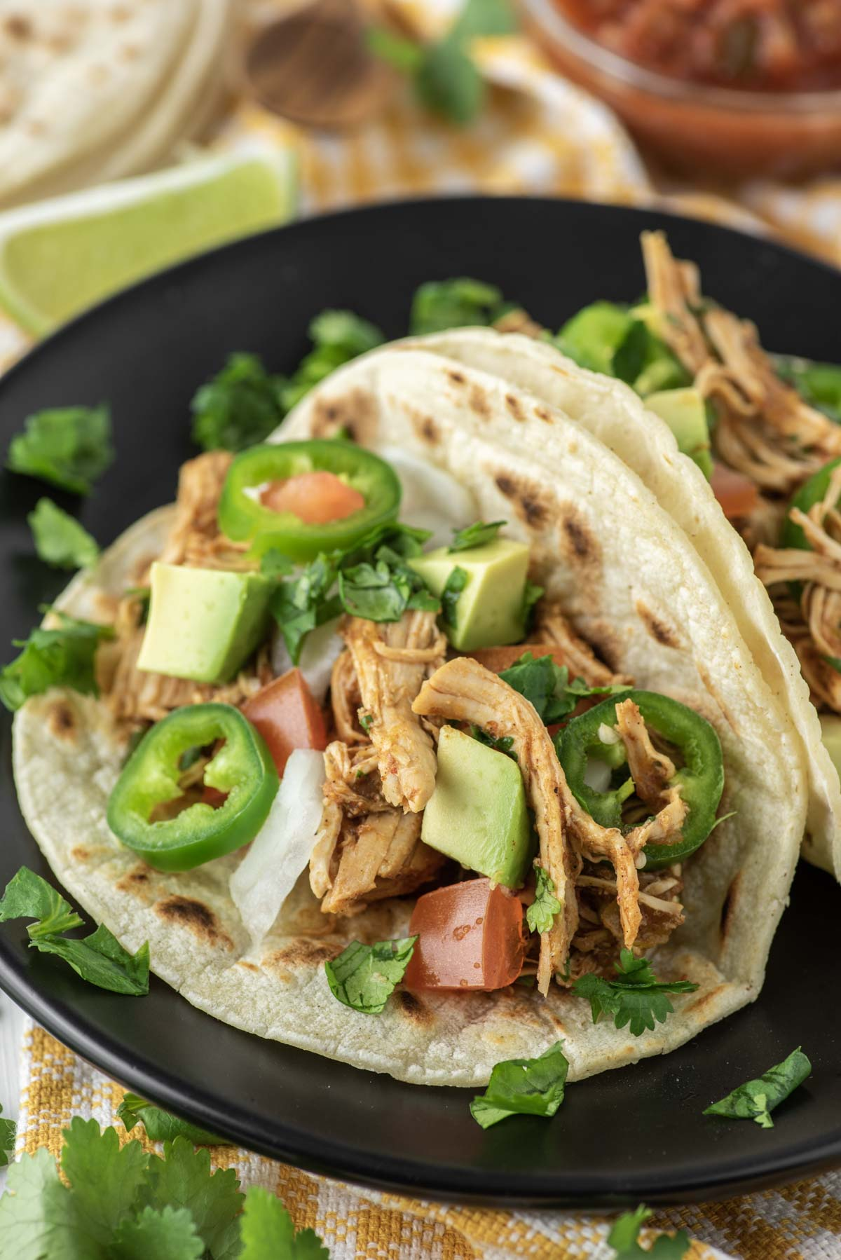 two Instant pot chicken tacos on black plate