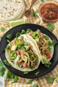 shredded chicken tacos on black pate