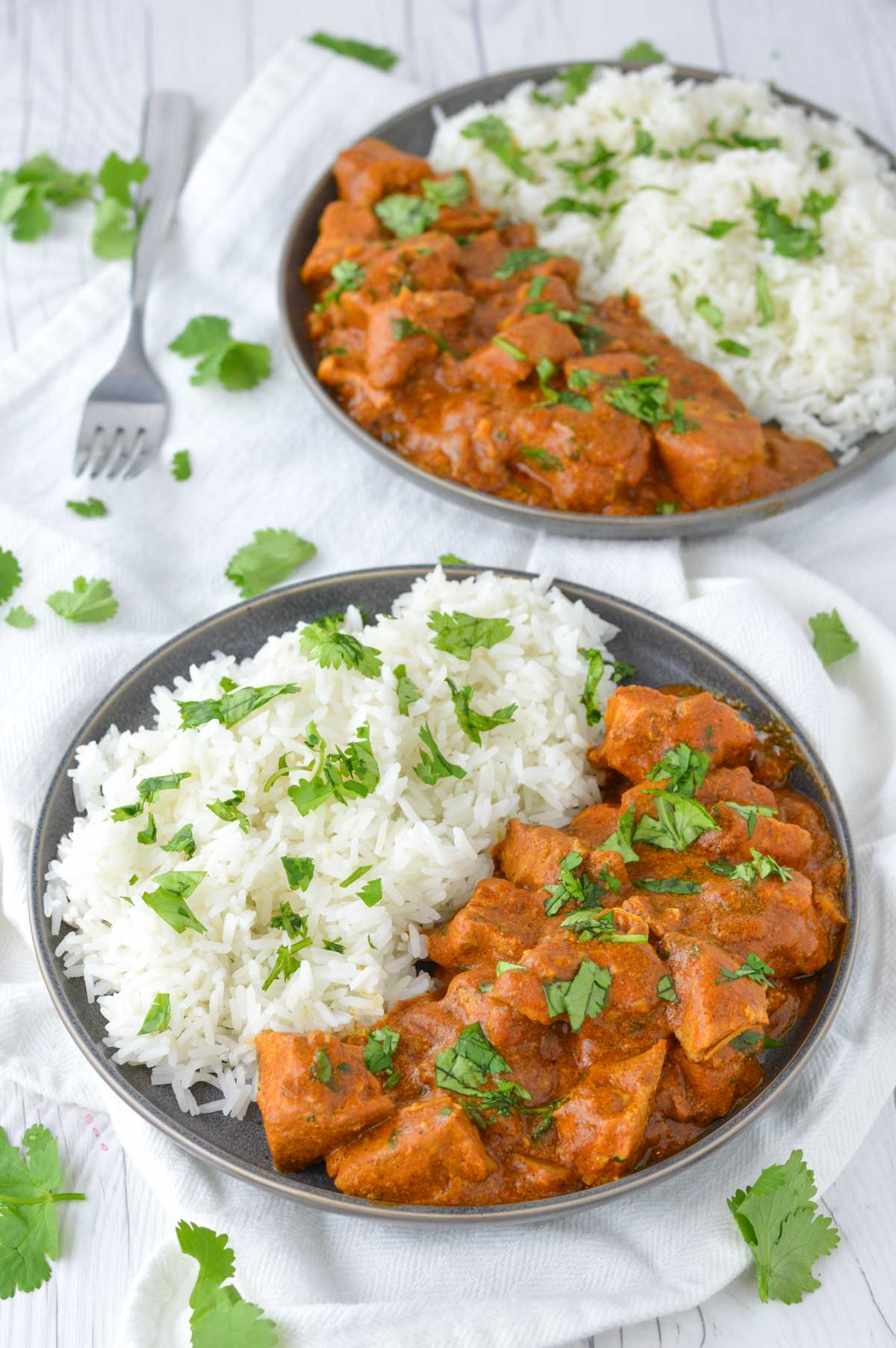 close-up of slow cooker Indian butter chicken in two slate plates