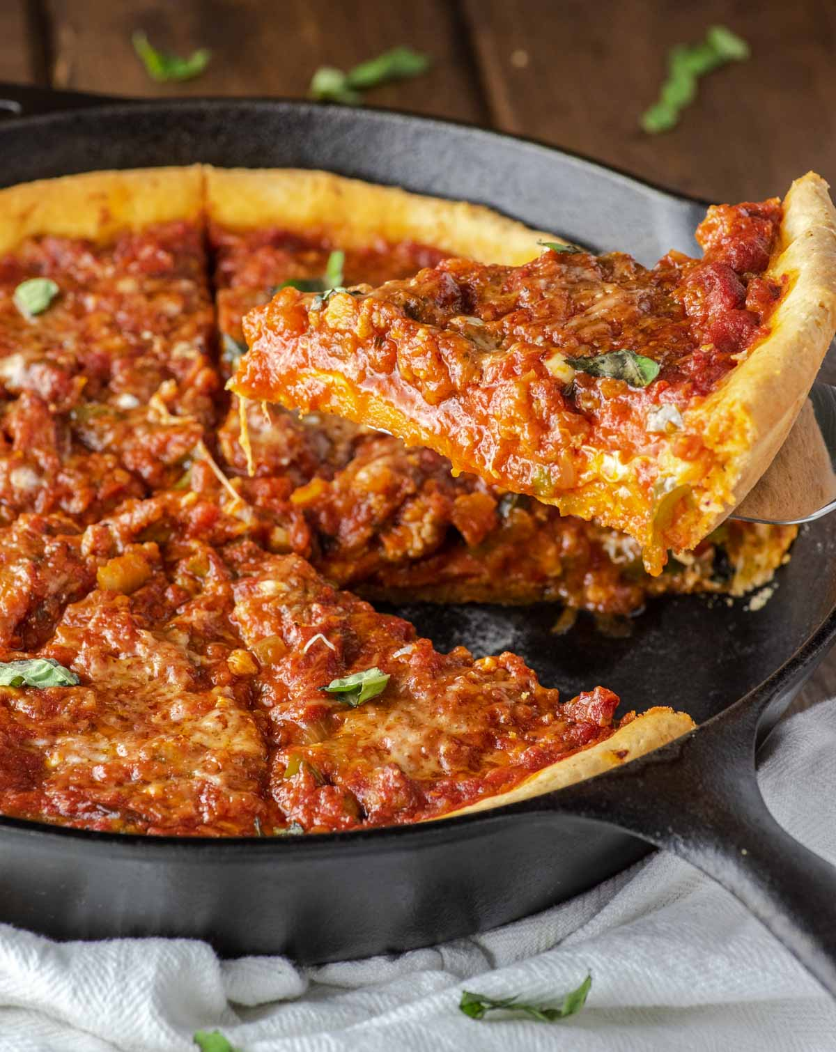 close-up of chicago-style deep dish pizza slice being pulled from skillet