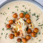 overhead shot of creamy roasted cauliflower soup in gray bowl