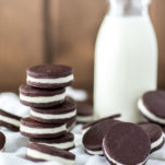 close-up of stacked oreo cookies on white kitchen towel with glass of milk