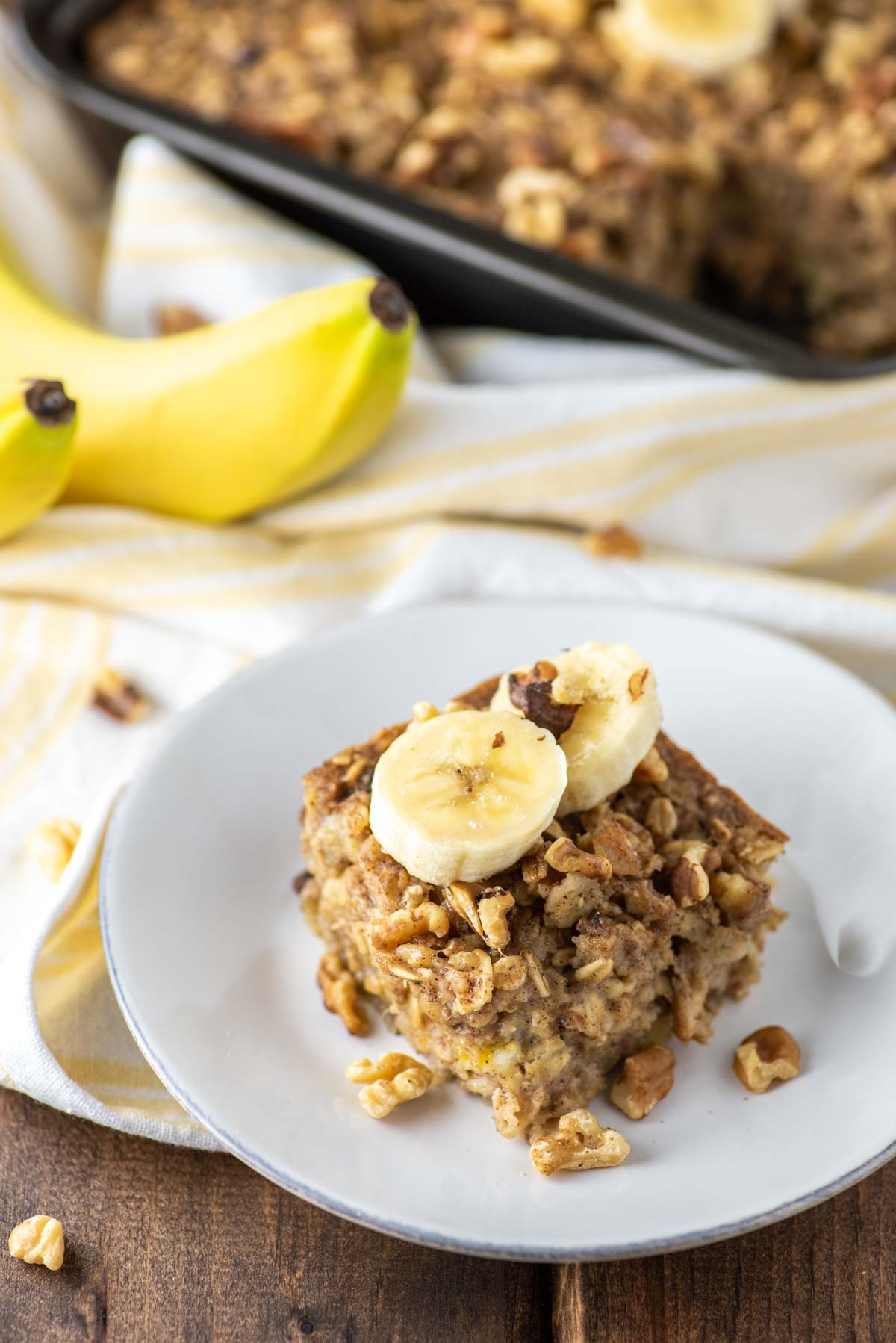 slice of banana baked oatmeal on white plate with pan in behind