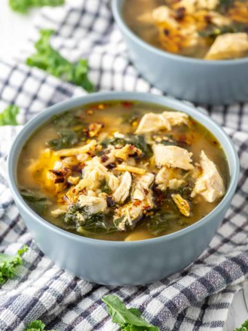 chicken barley soup in two blue bowls