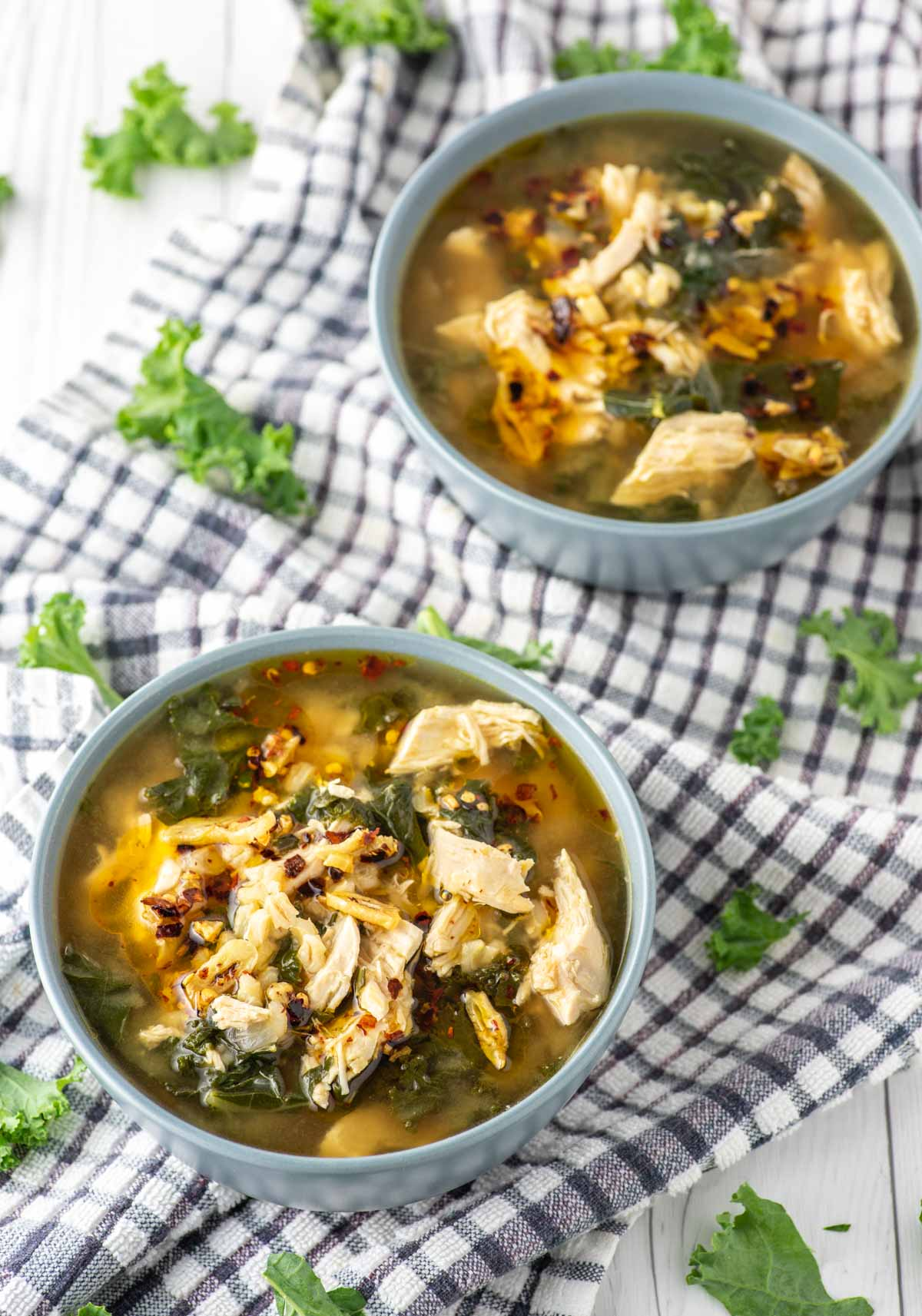 chicken barley soup in two blue bowls on dish towel