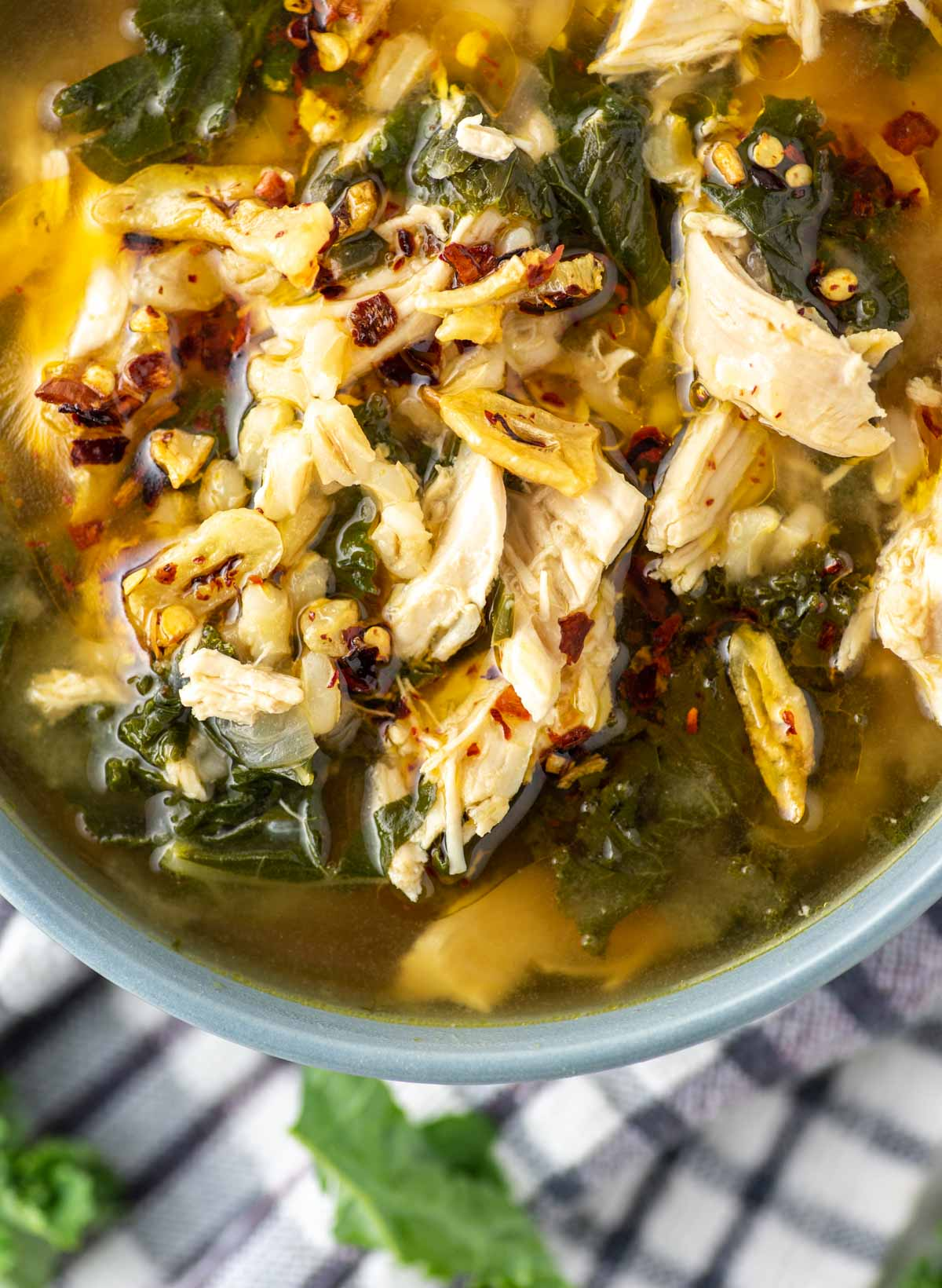 overhead shot of chicken barley soup in blue bowl