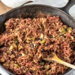 corned beef hash in skillet with wooden spoon and Guinness gravy in background