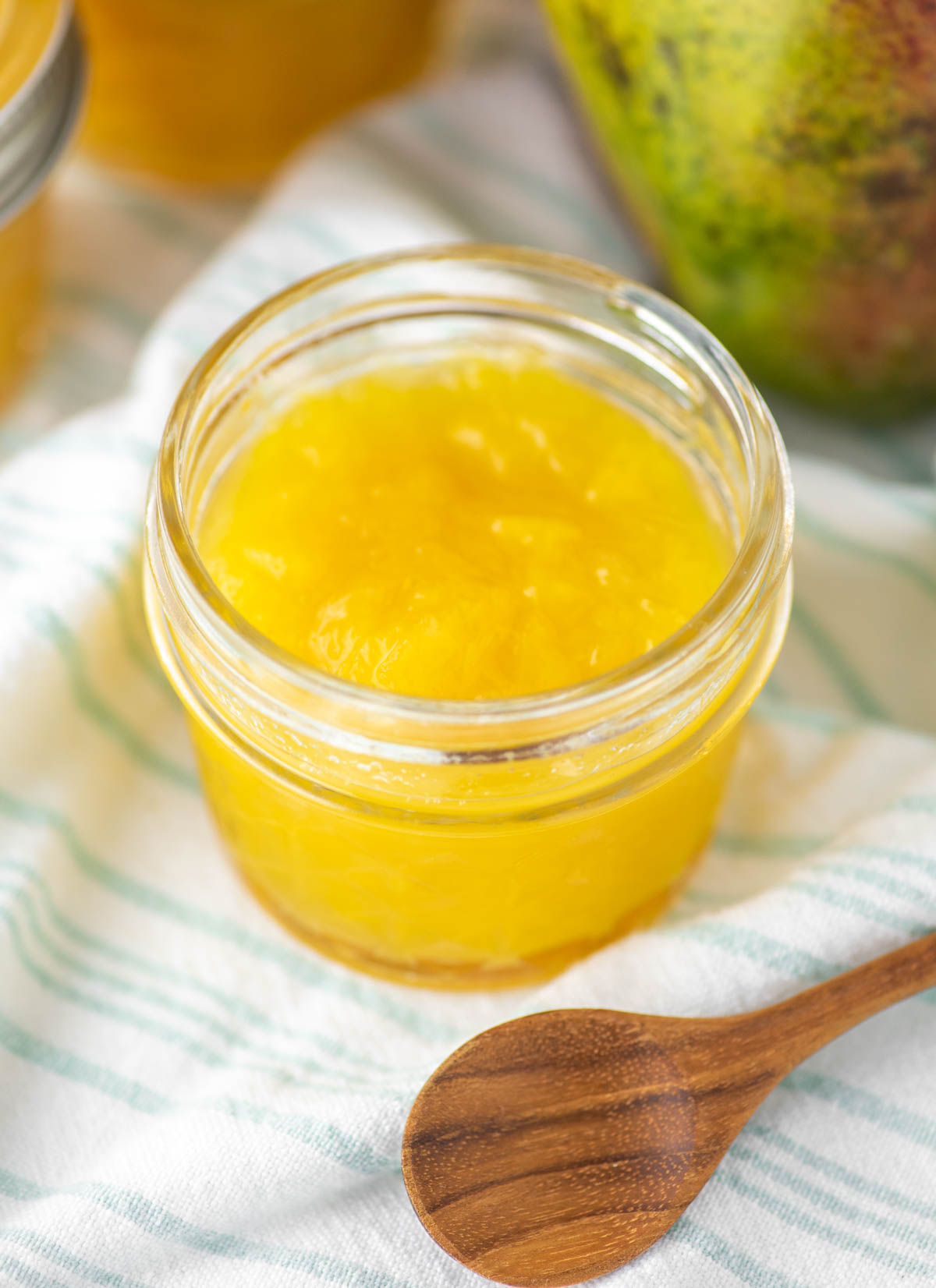 mango jam in glass jar on dish towel with wooden spoon