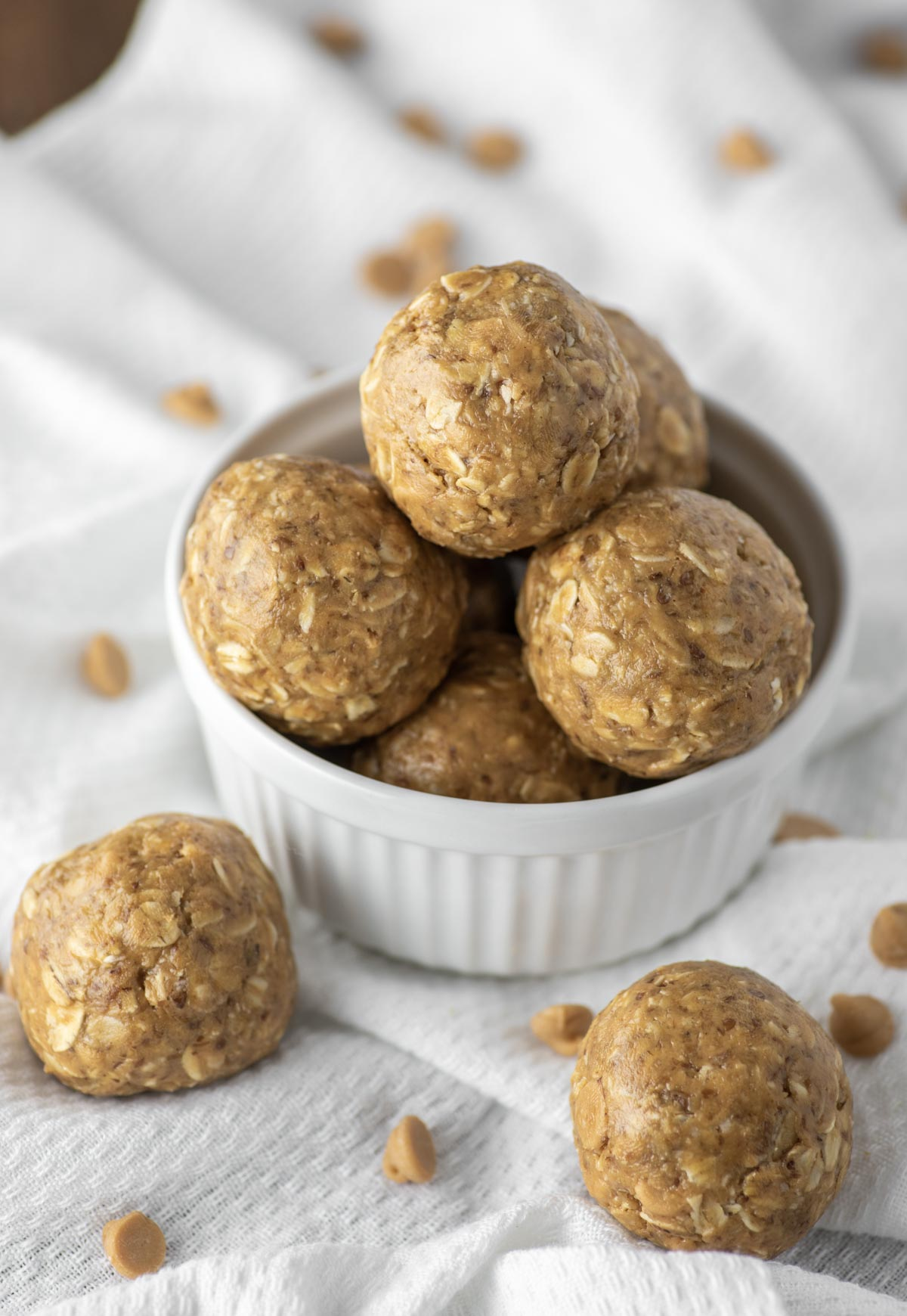 peanut butter energy balls in white ramekin on dish towel