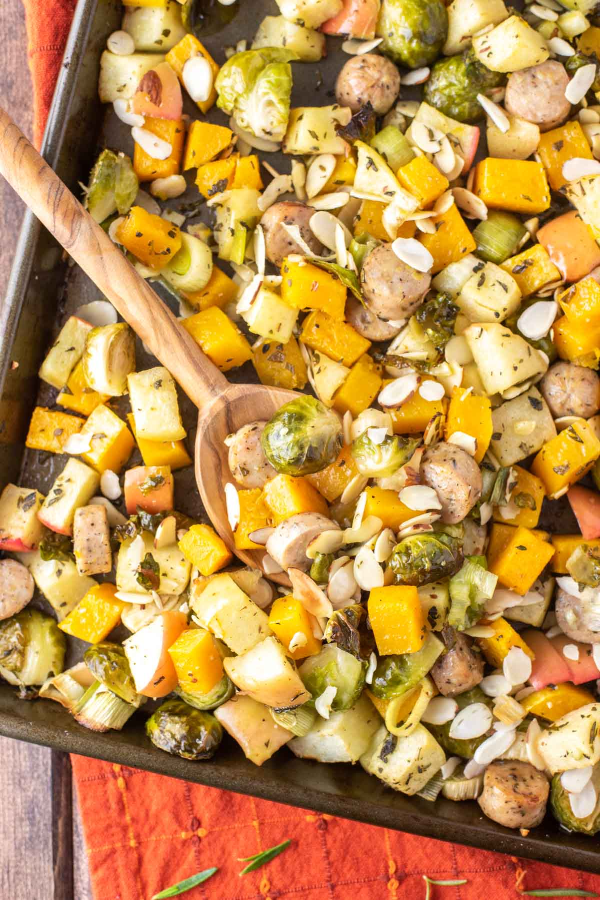 overhead shot of spoon dipped in autumn sheet pan sausage and veggies