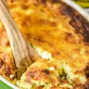 wooden spoon dipped in sweet corn pudding in green baking dish