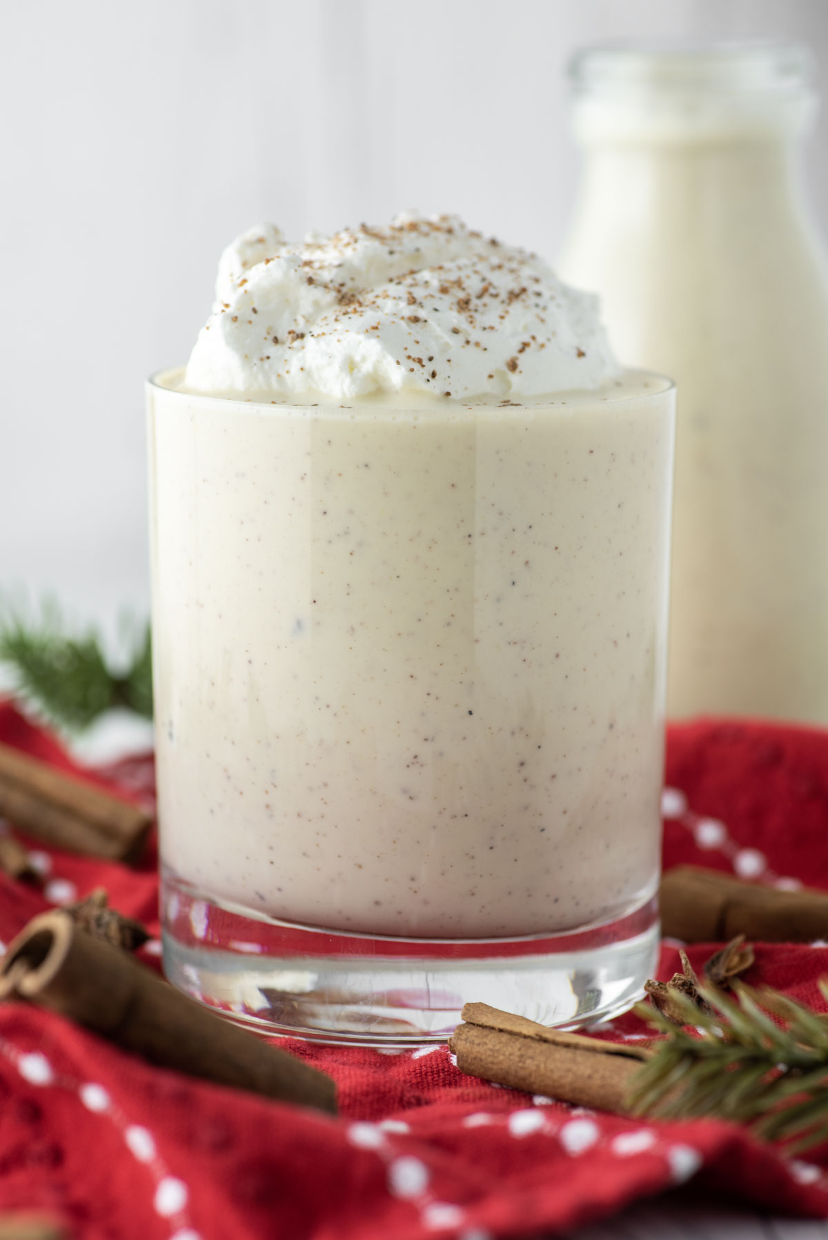 homemade eggnog in glass with whipped cream