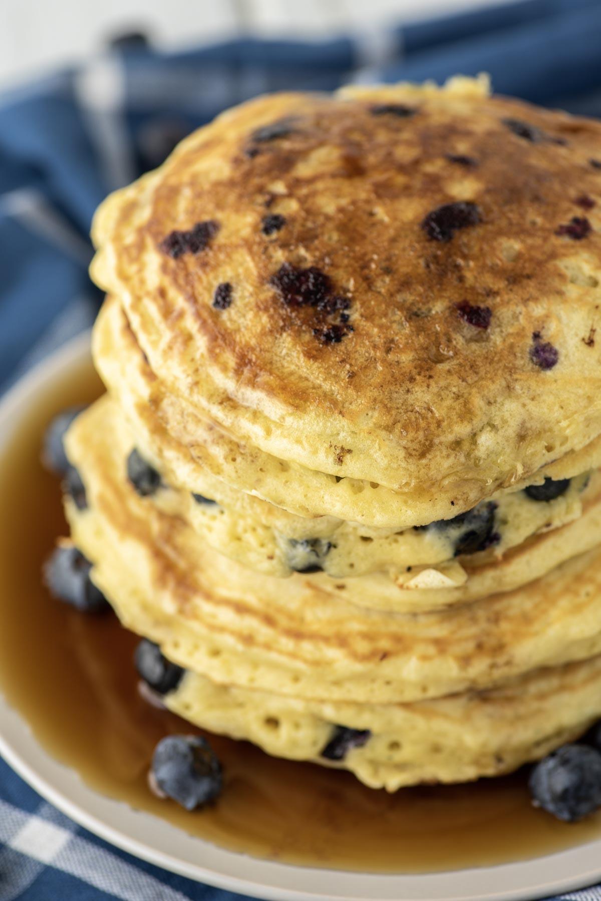 maple syrup on stacked blueberry pancakes