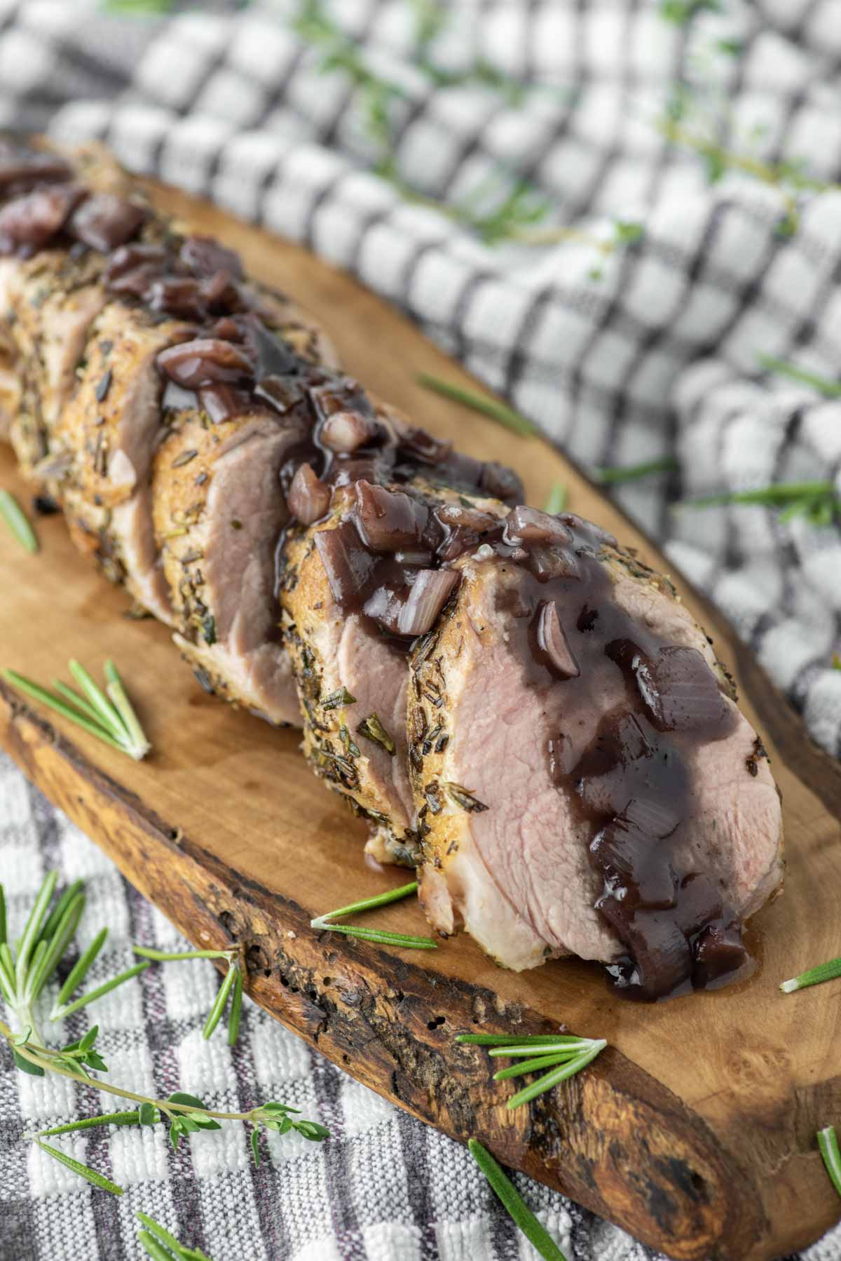 sliced rosemary pork tenderloin on wood board with red wine sauce