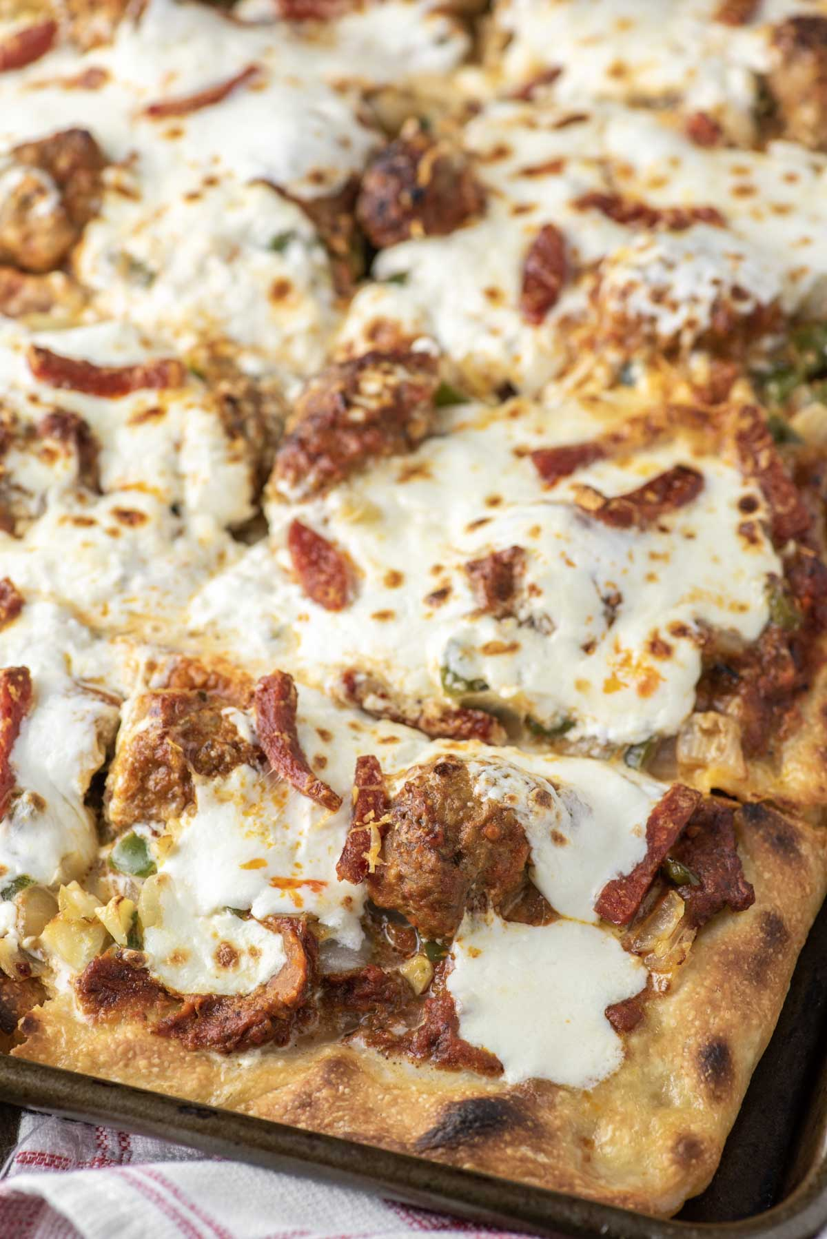 Sicilian-style pizza in sheet pan that is cut
