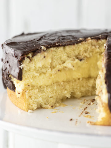 sliced Boston cream pie on white cake stand