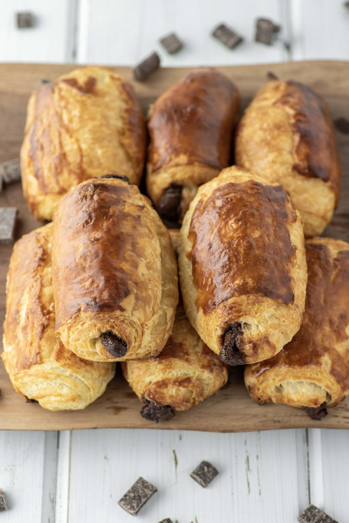 stacked chocolate croissants on wood cutting board