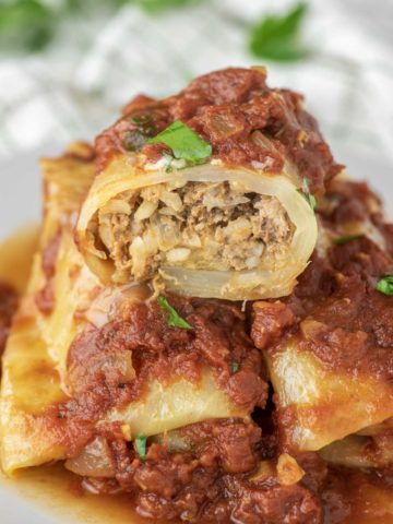 stuffed cabbage roll cut in half and stacked on two cabbage rolls