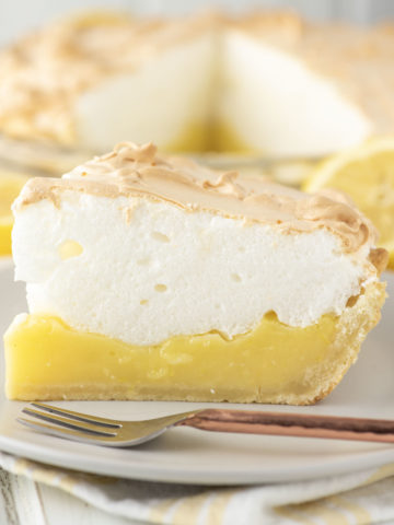 slice of lemon meringue pie with fork on plate