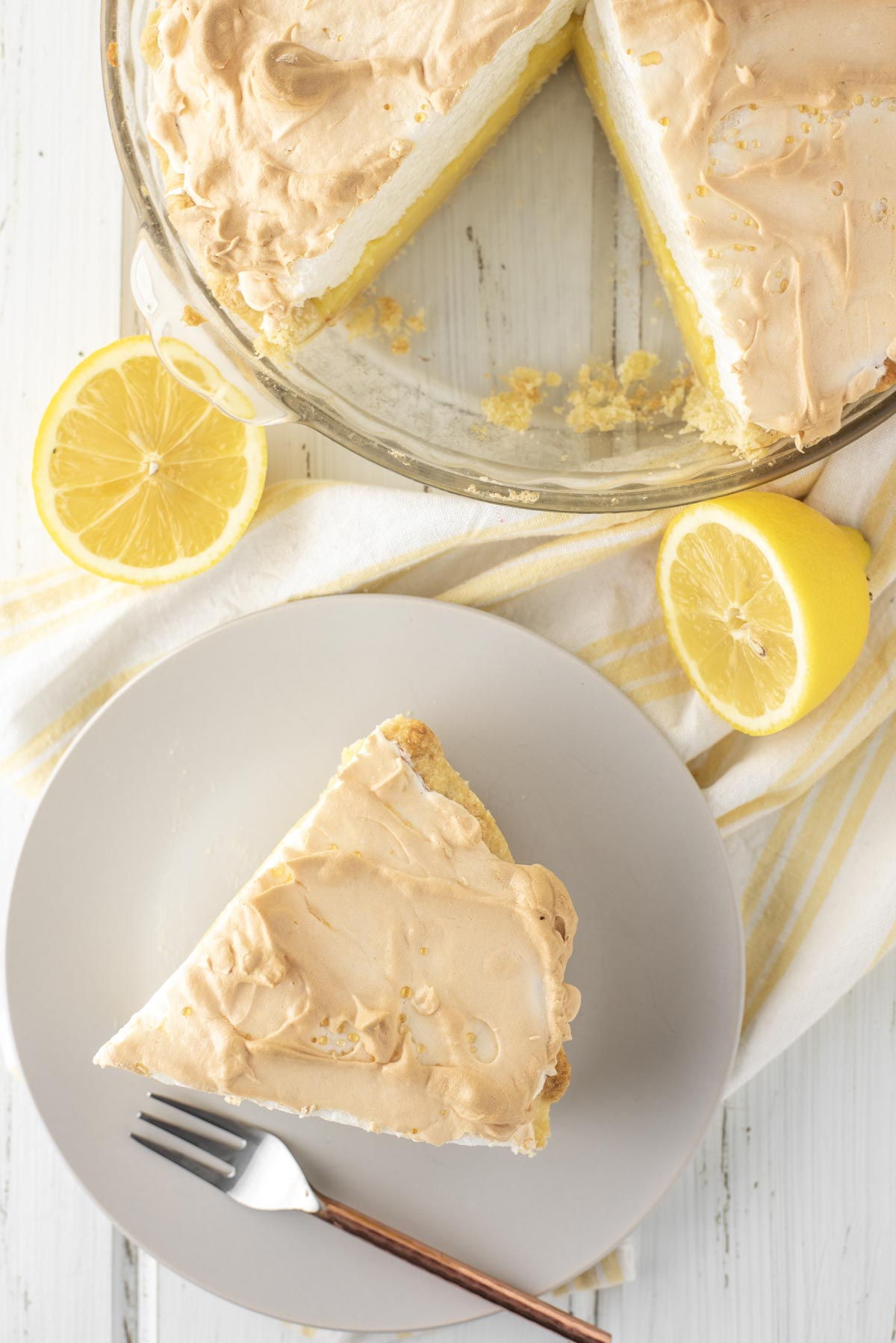 overhead shot of slice of pie on plate with rest of pie in glass dish