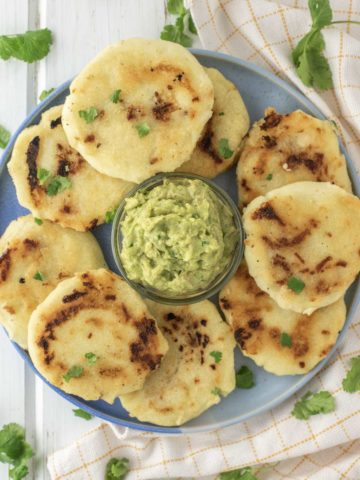overhead shot of Salvadoran pupusas on blue plate with guacamole