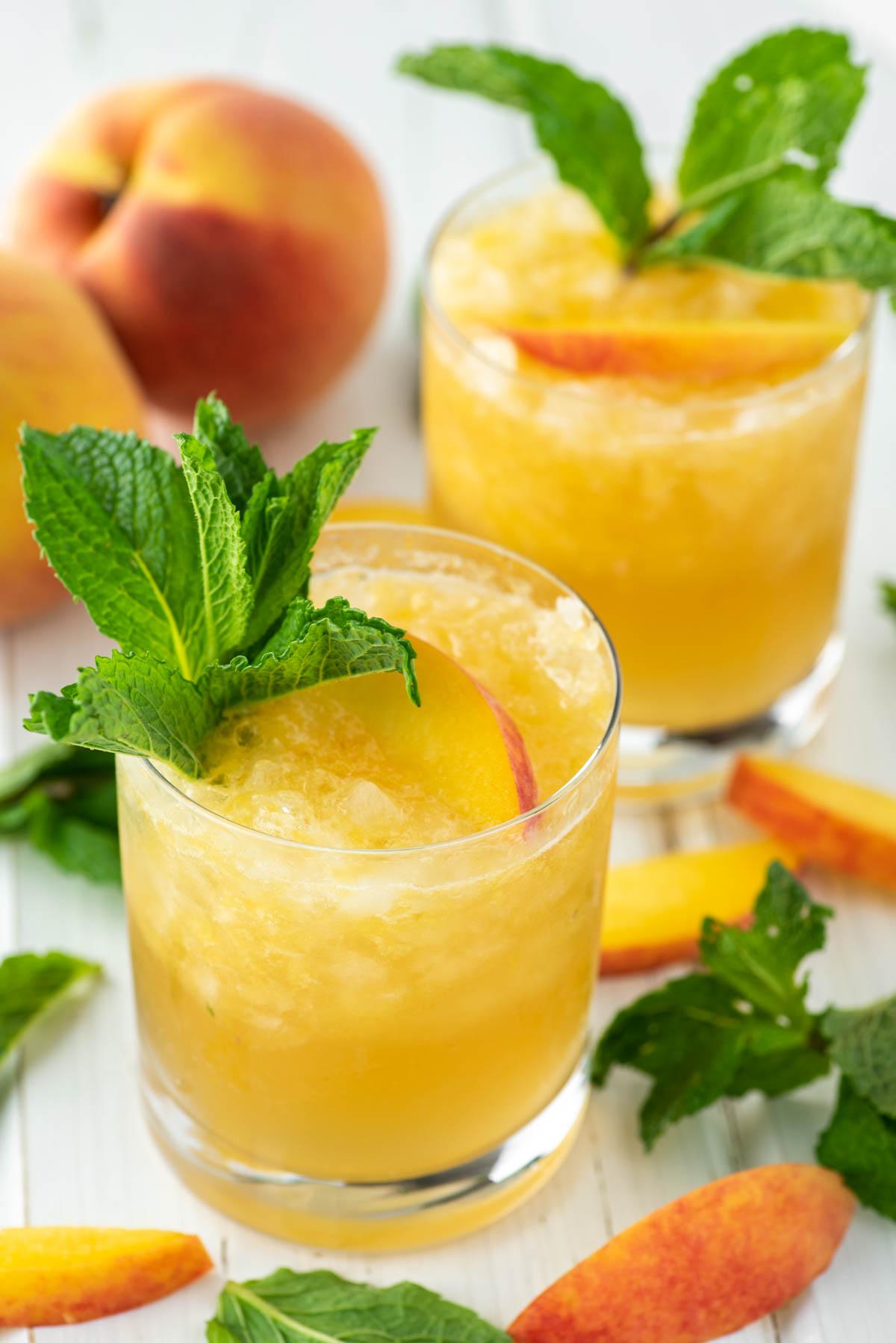 two glasses of bourbon peach smash cocktails