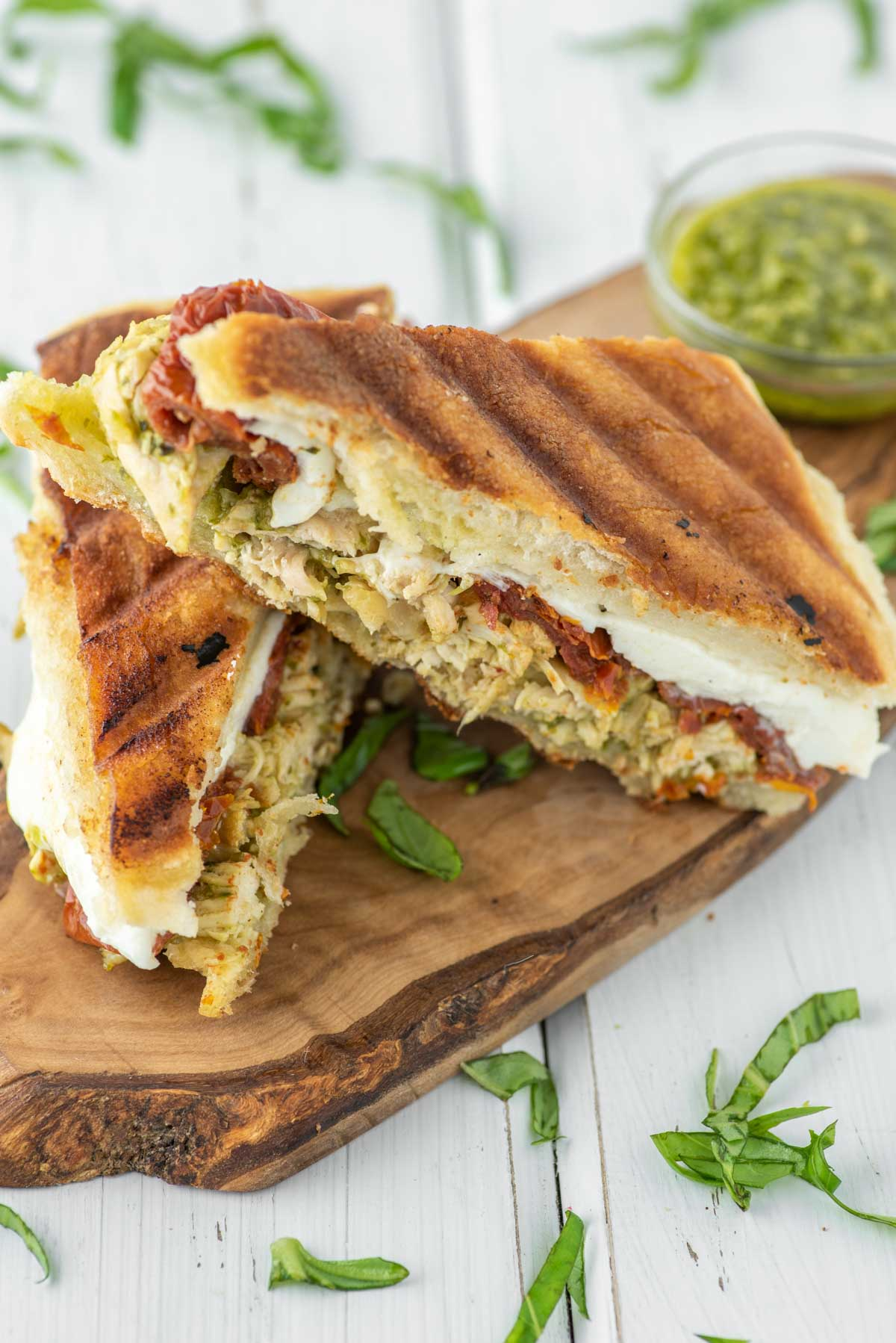 two slices of a chicken pesto panini on wood board with bowl of pesto in background