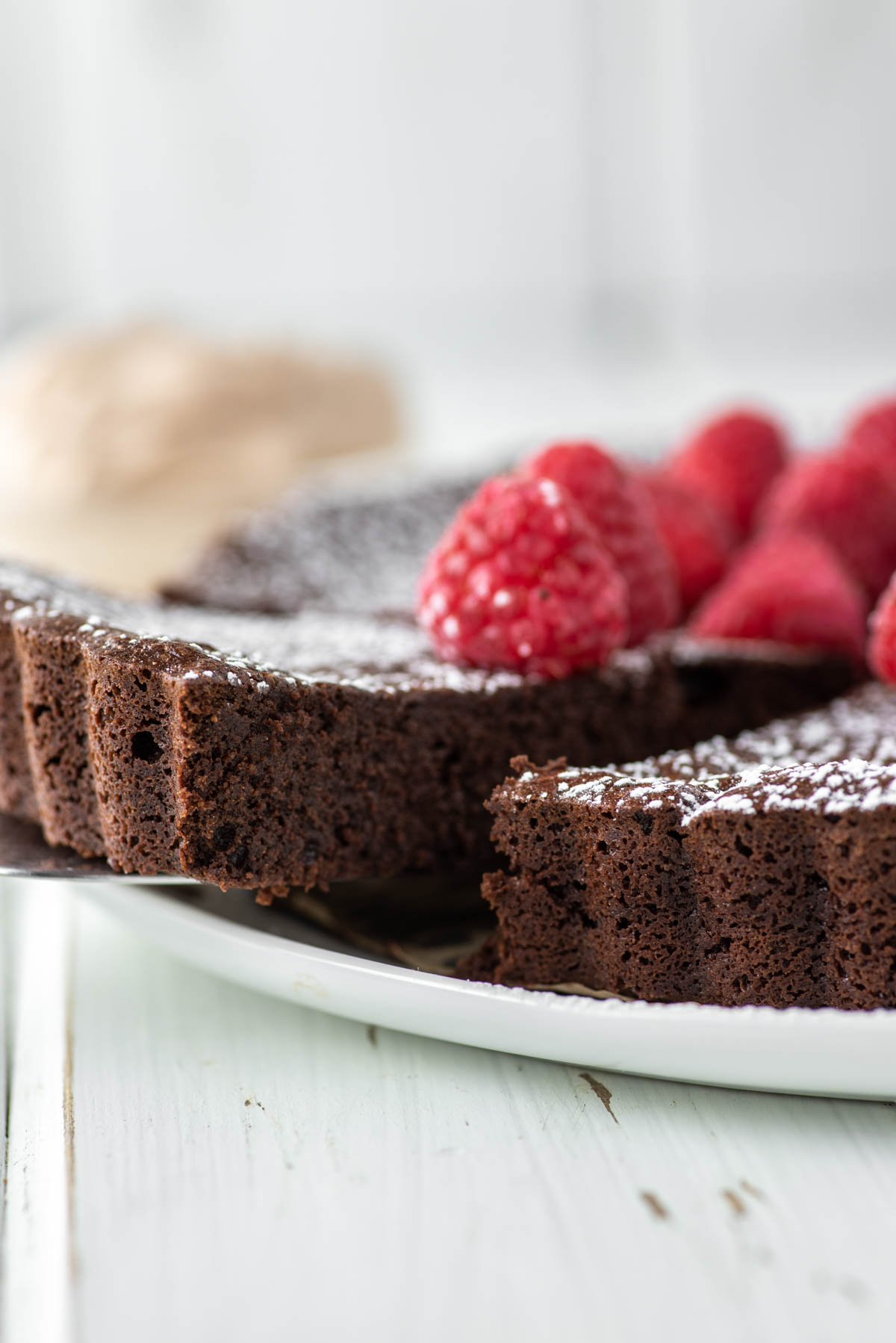 slice of flourless chocolate cake with being pulled away from white plate