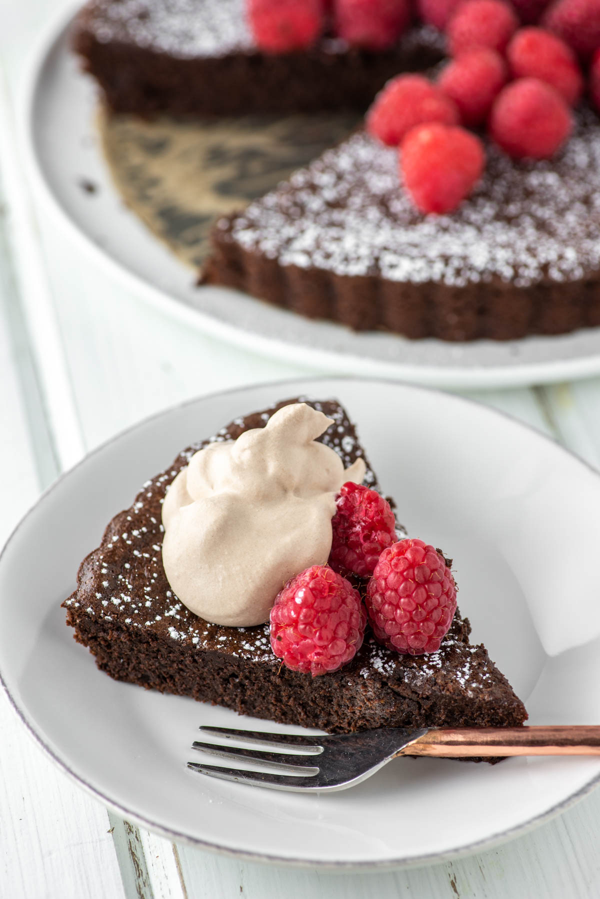 slice of flourless chocolate cake with raspberries and whipped cream on white plate